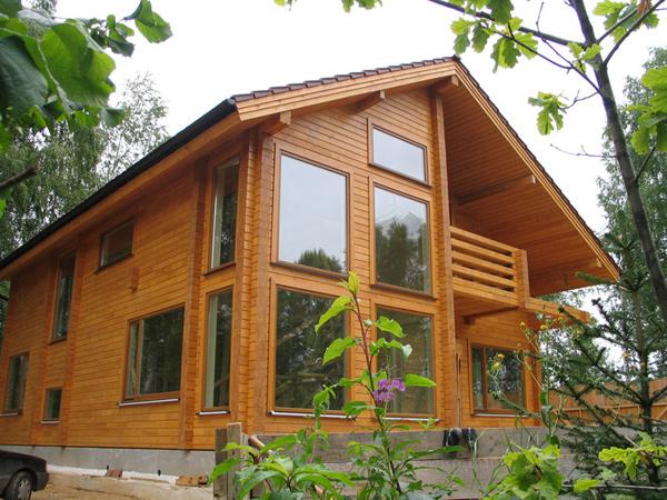 трехэтажный дом из дерева с двумя балконами